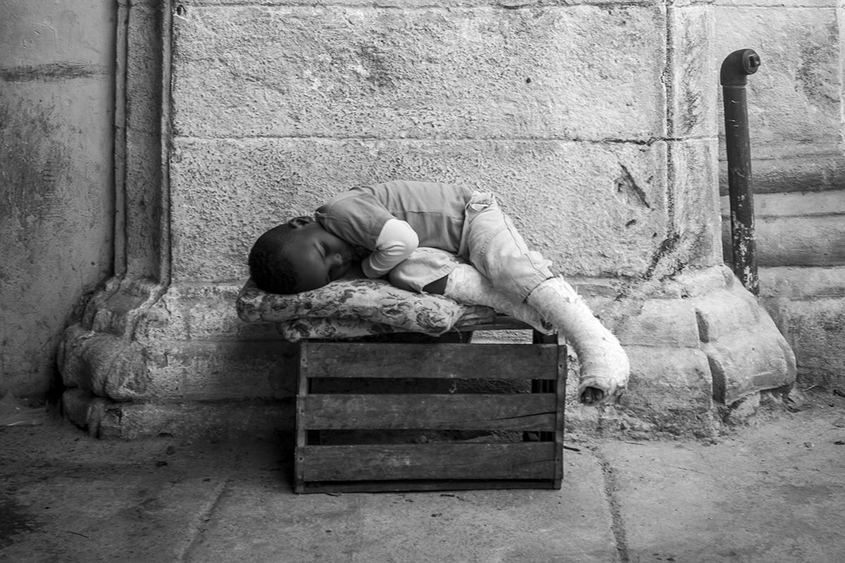 Nap Time A boy with broken legs naps on a wooden box behind his father's fruit stall in Havana, Cuba.