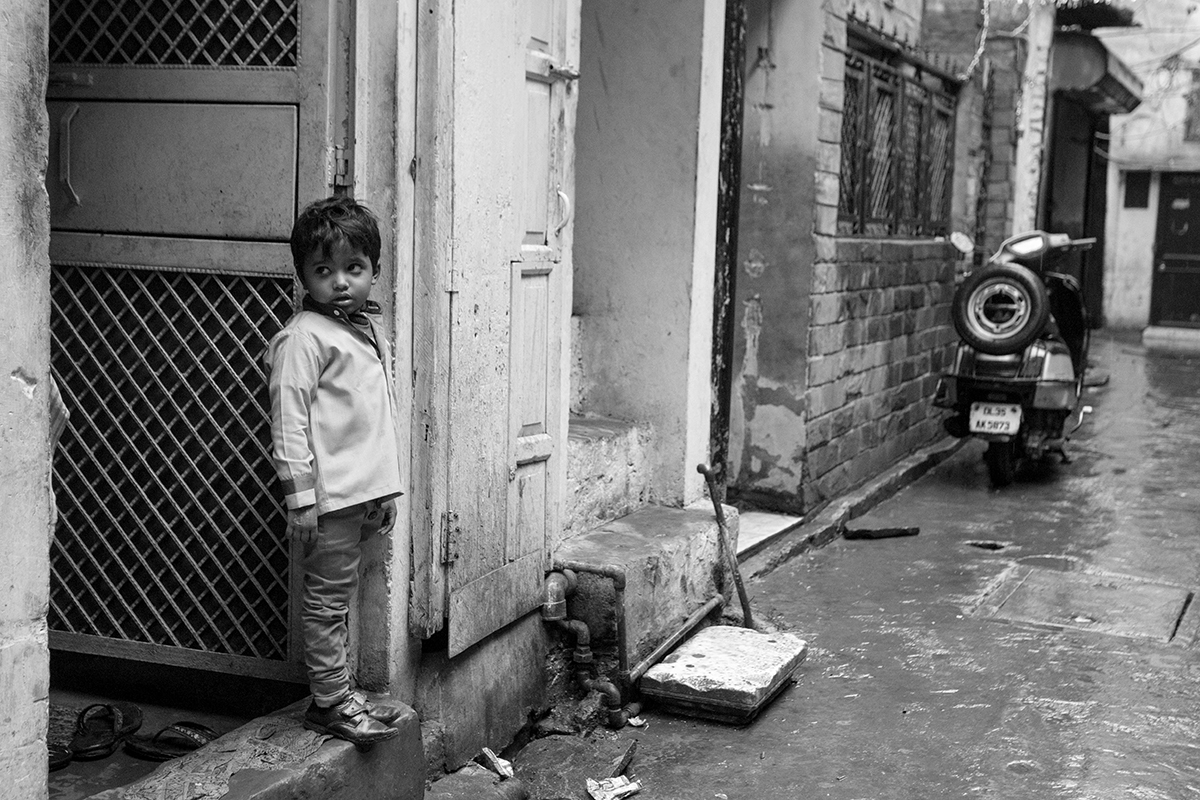 After the Rain Child stands outside of his door waiting for his sister to arrive from school in New Delhi, India.