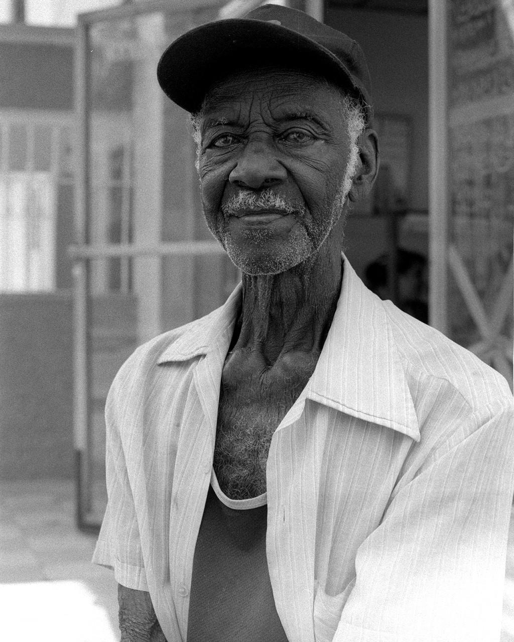 Sentado num muro da esplanada da bodega local El Crucero em Santa Clara, Mário de 93 anos conta o seu percurso pelos campos de cana de açucar.
