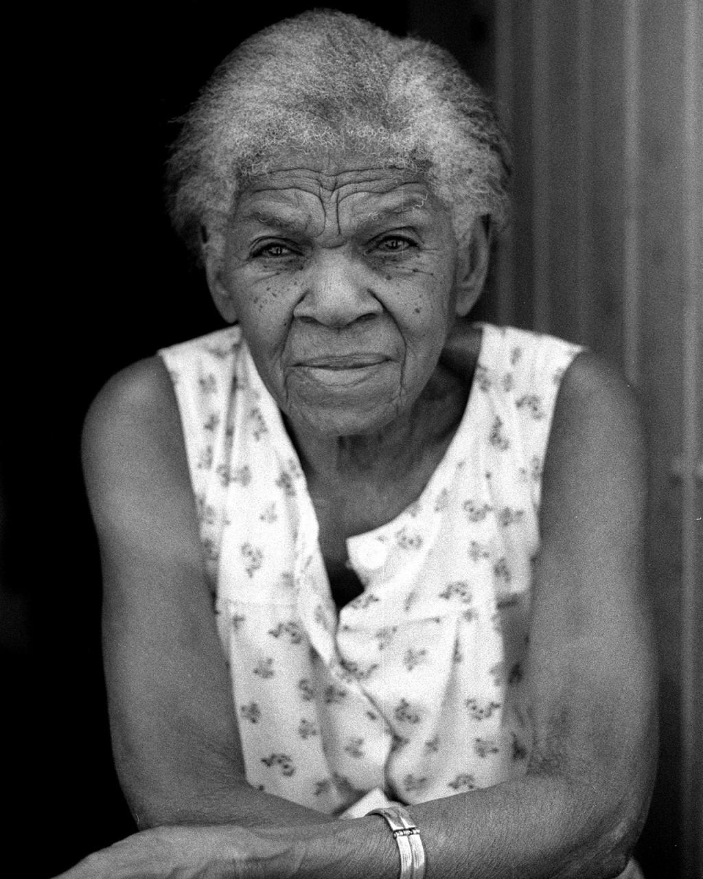 Senhora sentada à porta em Santiago de Cuba.