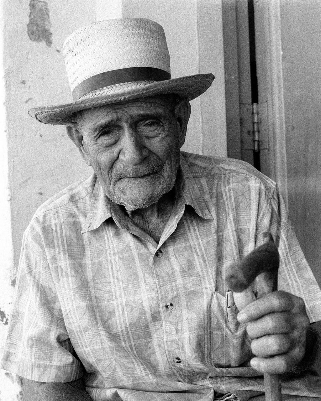 Um senhor aposentado passa muito do seu tempo à porta de casa em Trinidad, já que lhe é difícil caminhar.
