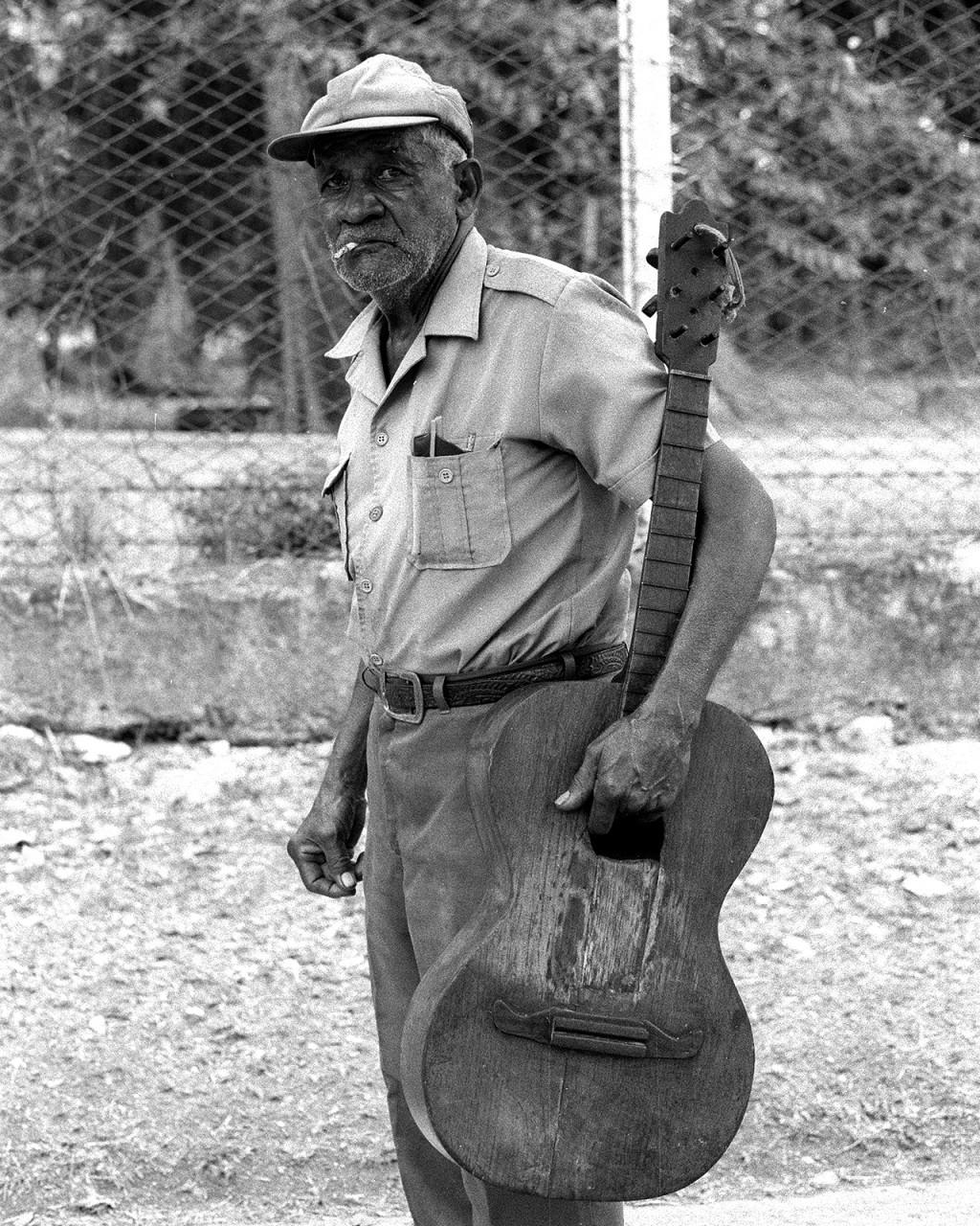 Um senhor caminha pelas ruas de Santa Clara carregando uma guitarra com bastante uso e com falta de cordas.