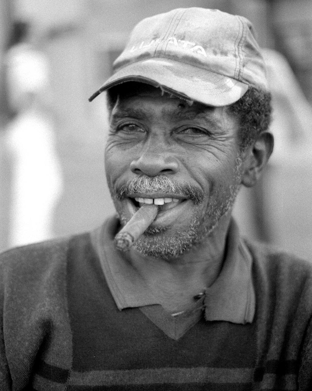 Um vendedor de rua sentado no seu carro de mão em Santiago de Cuba, fumando o seu charuto antes de começar o dia.